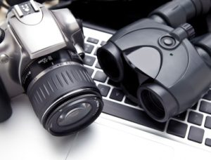Camera and binoculars on keyboard. Concept for private investigation.